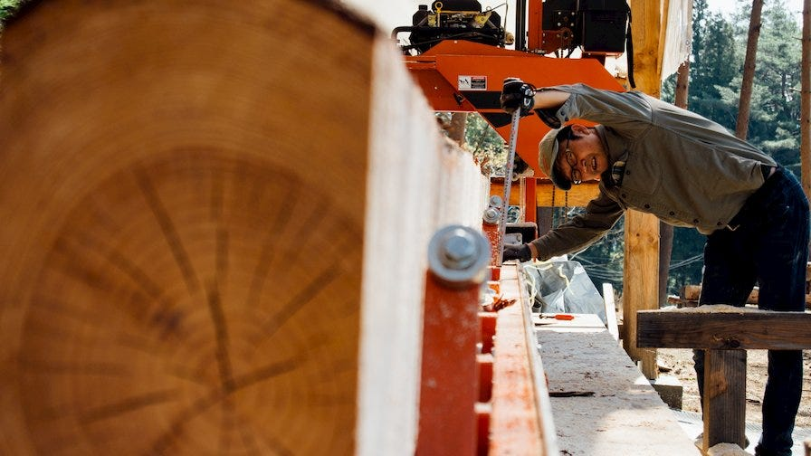 Woodworker turning a log on a portable sawmill